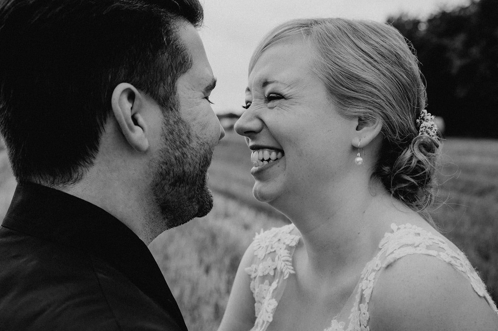 Braut lacht ihren Bräutigam an beim Fotoshooting auf einem Stoppelacker fotografiert von Hochzeitsfotograf Darmstadt