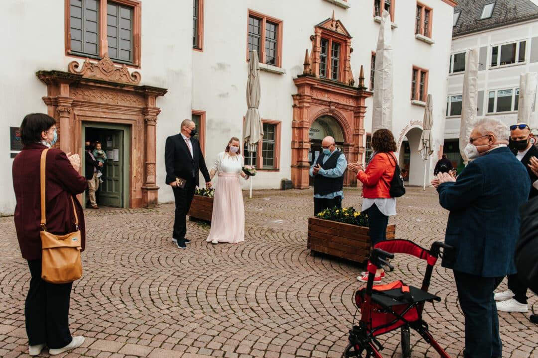 Familie applaudiert als das Brautpaar aus dem Standesamt Darmstadt herauskommt.