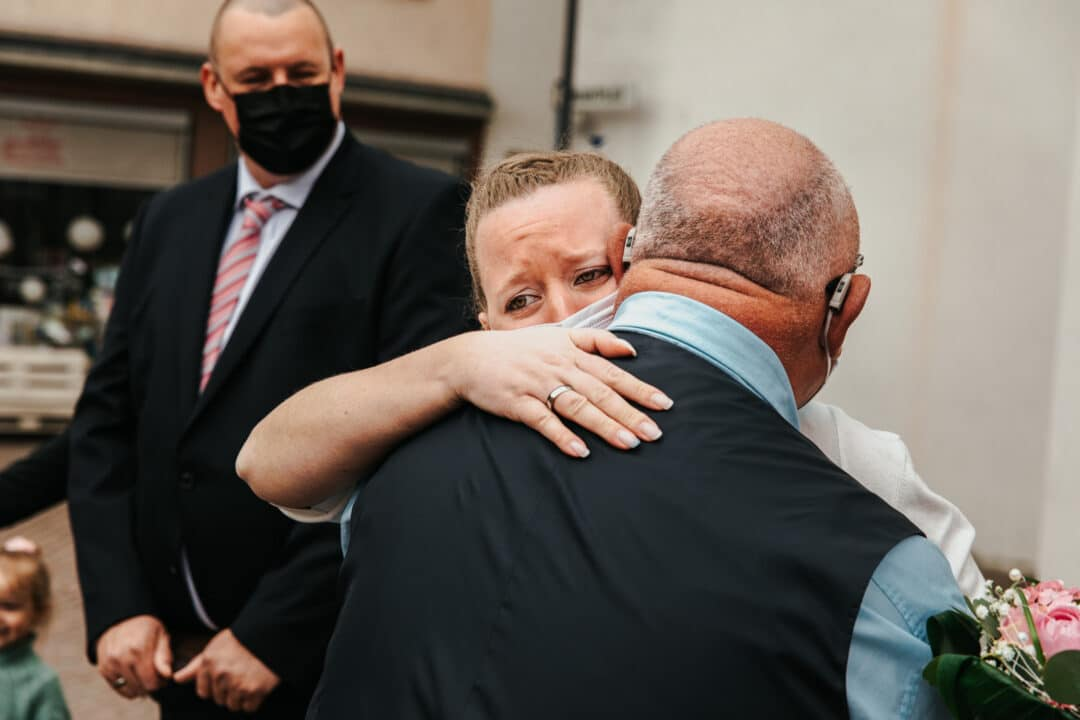 Braut weint und umarmt ihren Vater vor dem Standesamt Darmstadt