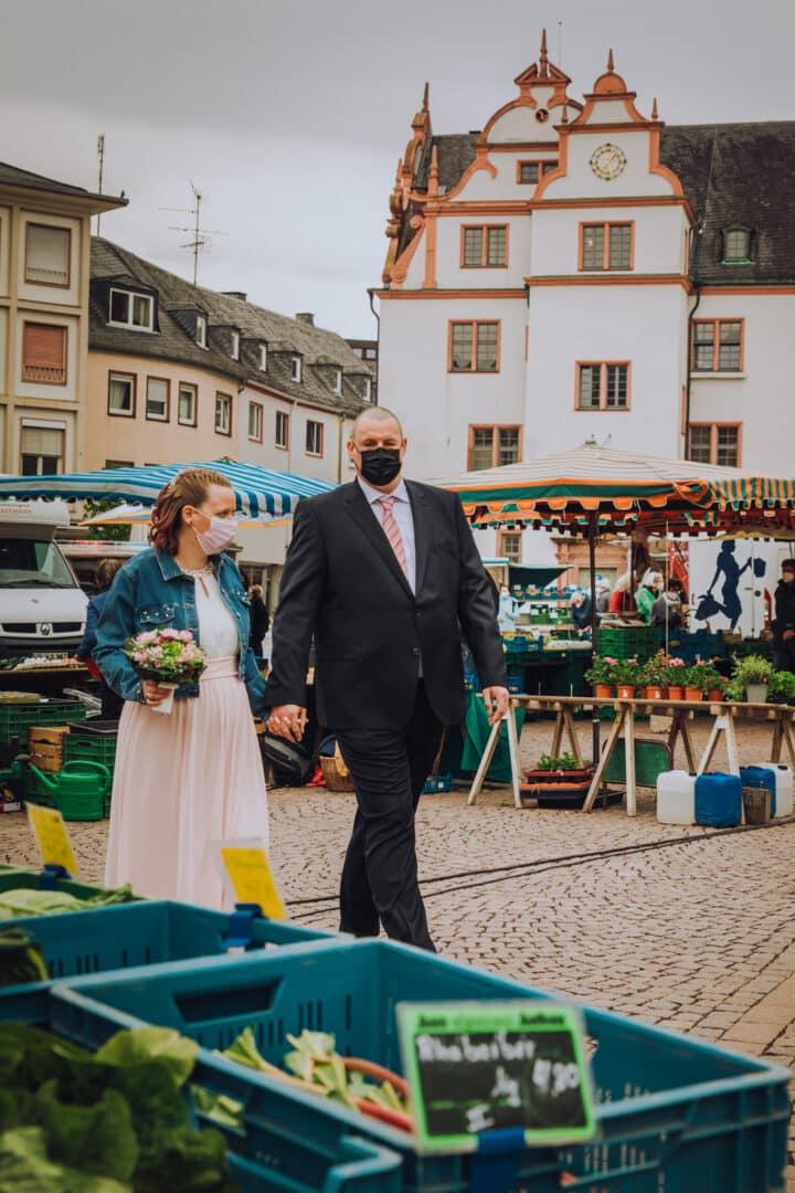 Brautpaar läuft über den Marktplatz zwischen den Marktständen entlang