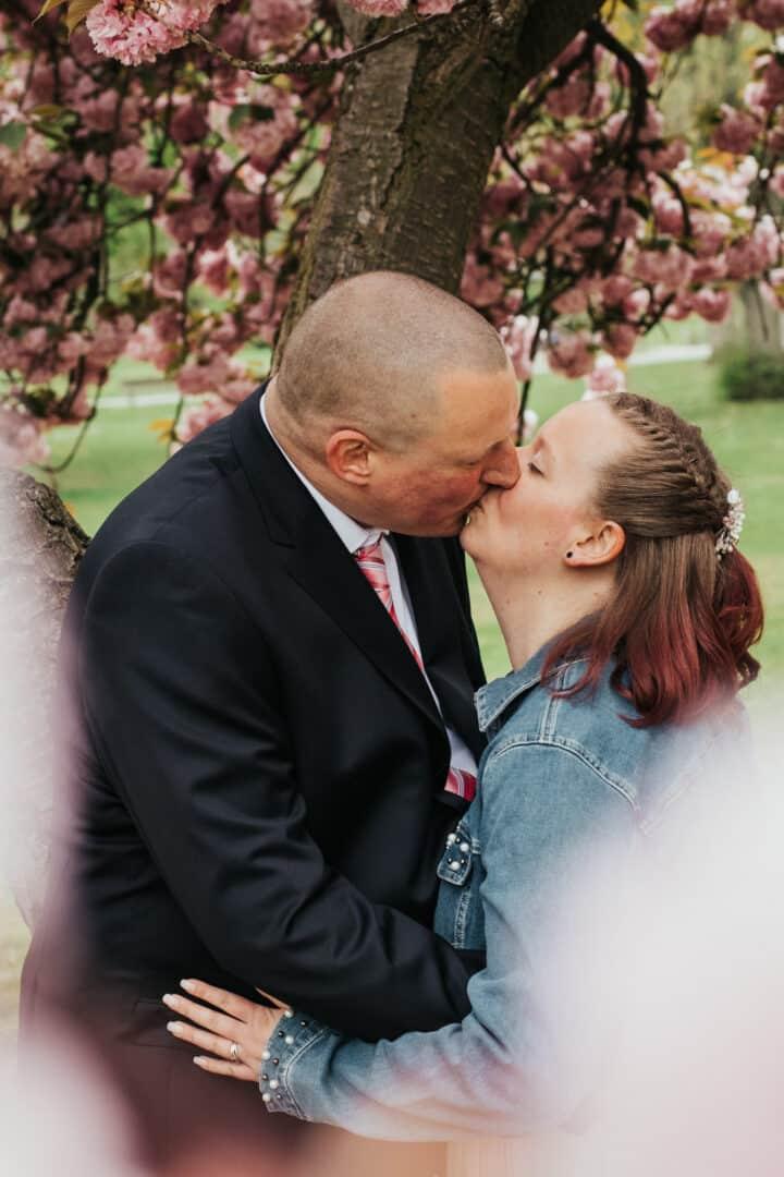 Braut und Bräutigam küssen sich unter dem blühenden Kirschbaum im Herrngarten Darmstadt