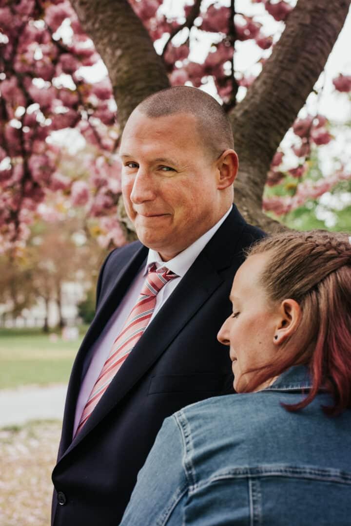 Bräutigam lacht verschmitzt in die Kamera blühenden Kirschbaum im Herrngarten Darmstadt