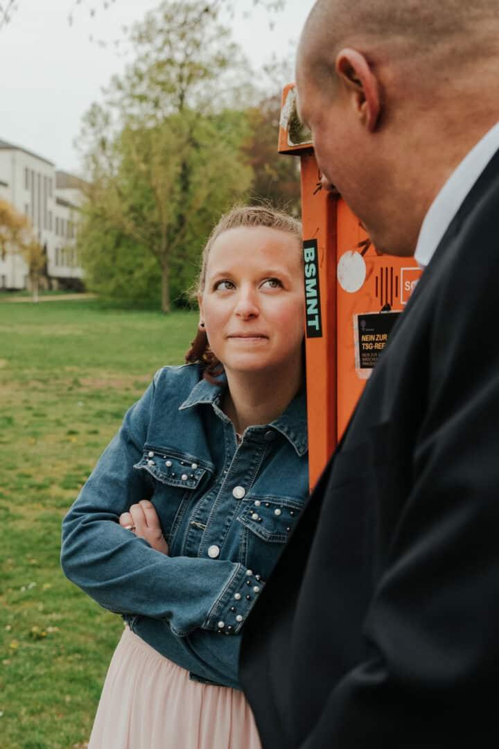 Braut lehnt an Feuermelder im Herrngarten Darmstadt beim Brrautpaar Fotoshooting.