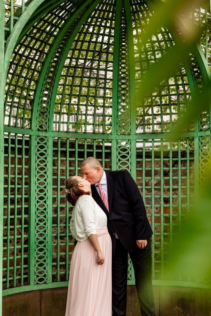 Mann küsst seine Frau mit Babybauch im Prinz-Georg-Garten Darmstadt