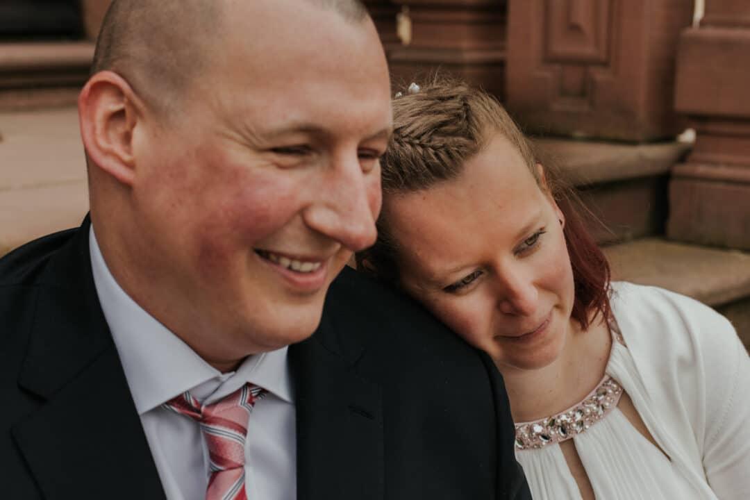 Braut lehnt ihren Kopf an die Schulter ihres Mannes im Prinz-Georg-Garten Darmstadt