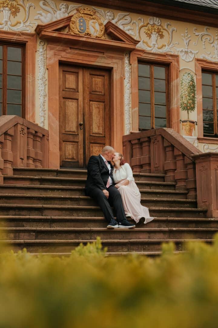 Braut und Bräutigam sitzen auf einer Treppe im Prinz-Georg Garten Darmstadt und küssen sich.