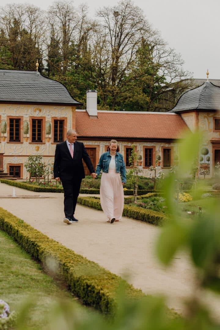 Ein Brautpaar läuft Hand in Hand einen Weg im Prinz-Georg Garten entlang
