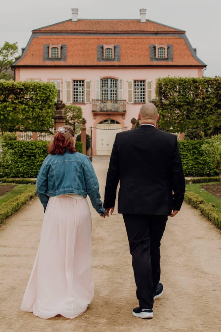 Braut und Bräutigam laufen auf ein Gebäude im Prinz-Georg Garten zu, dem Museum.