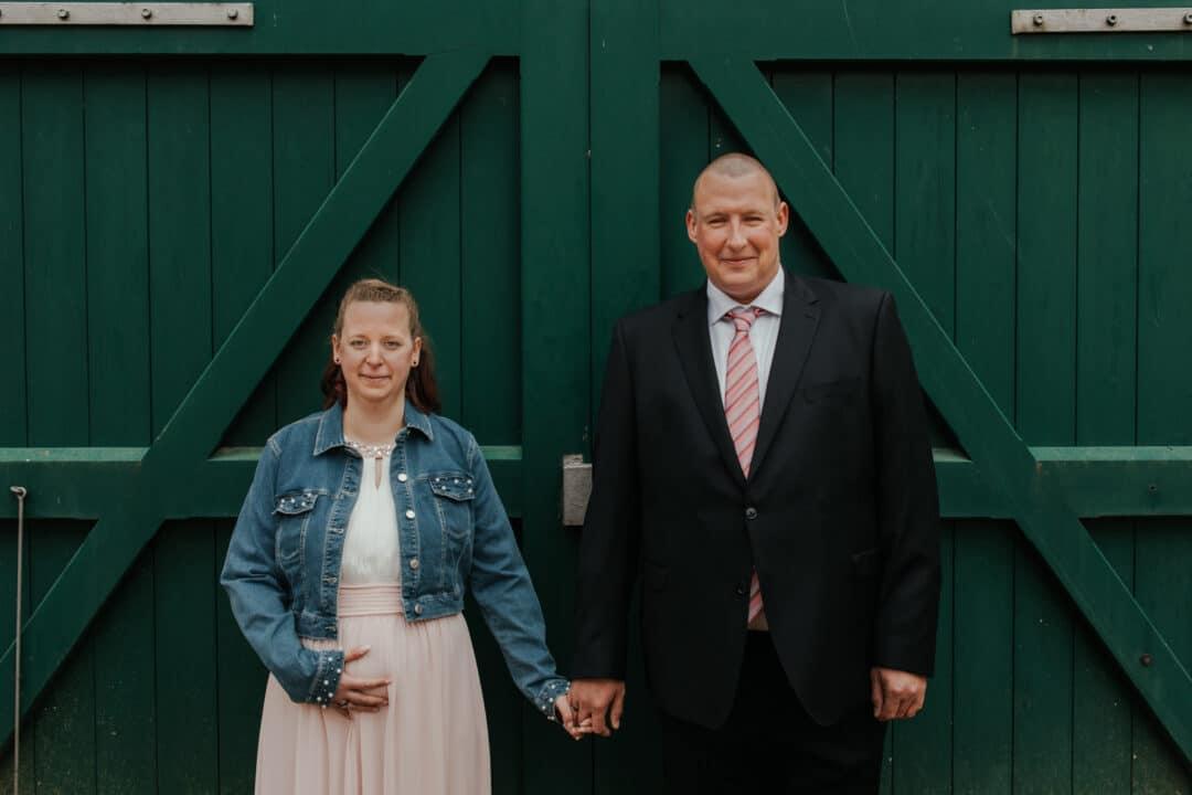 Bräutigam und Braut stehen vor einem Tor im Prinz-Georg Garten