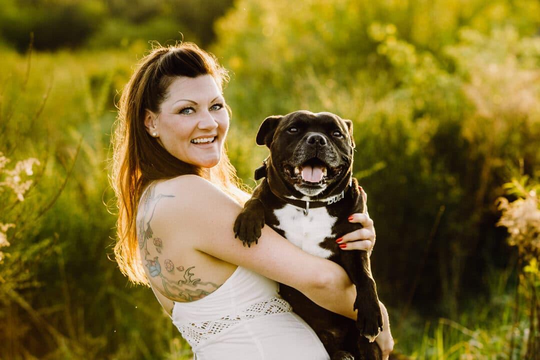 Frau mit Pitbull beim Hundeshooting im grünen bei Sonnenuntergang