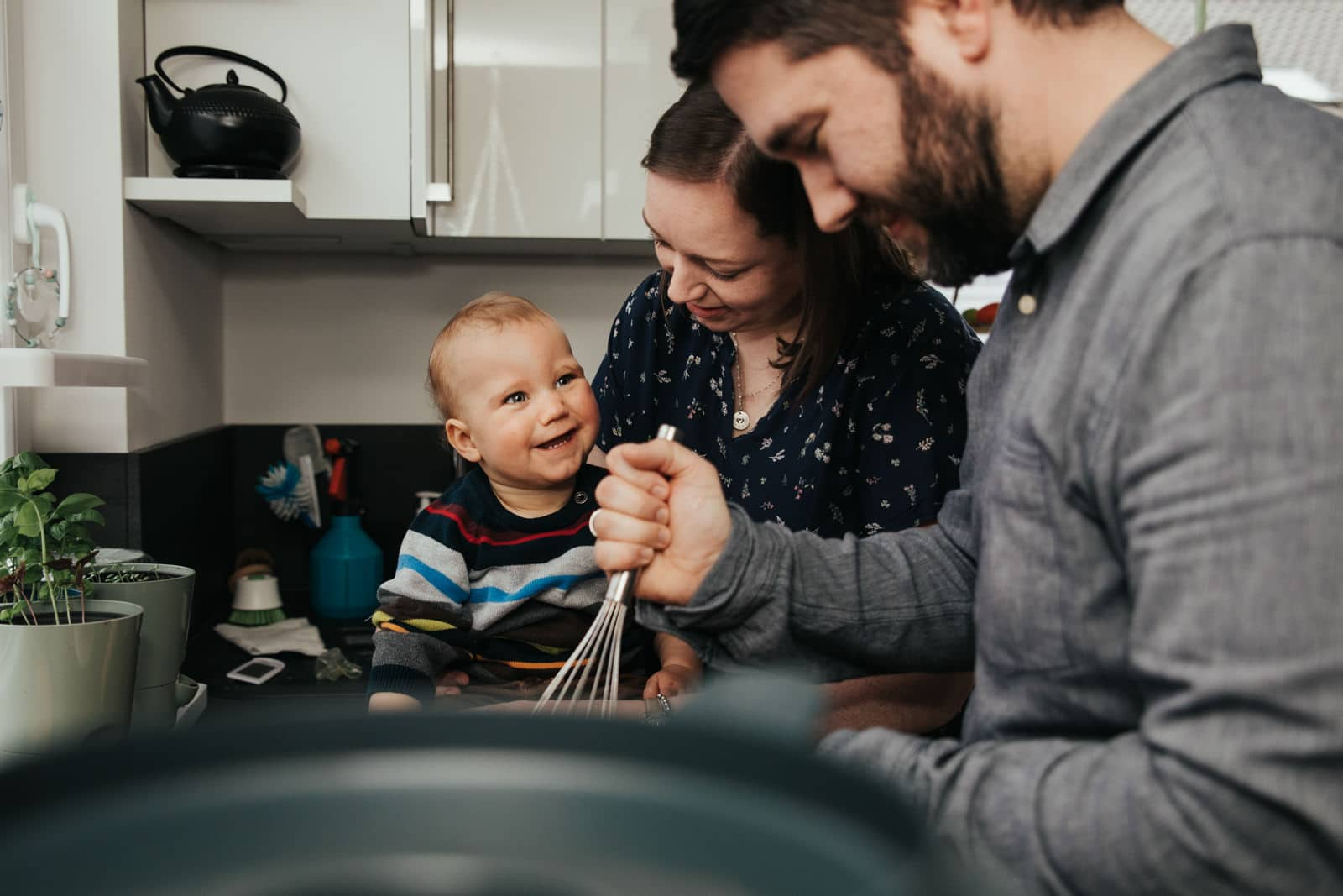 Eine Familie zu dritt ist in der Küche und backt zusammen während der kleine Junge freudig lacht.