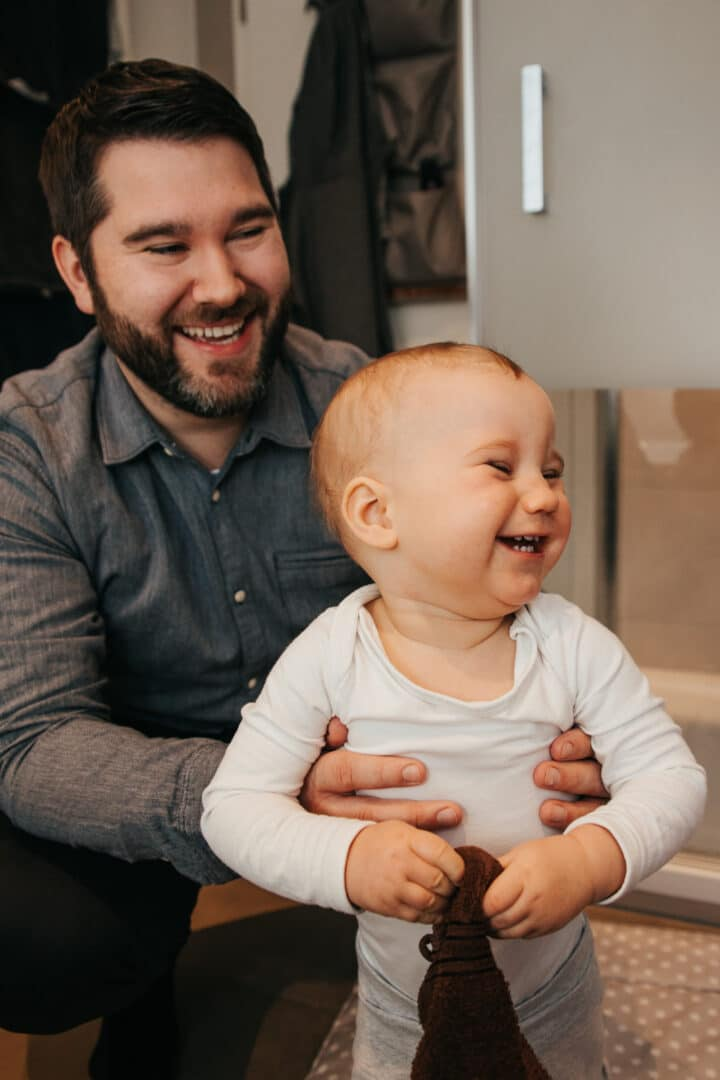 Ein Vater hält seinen kleinen Sohn fest und beide lachen.