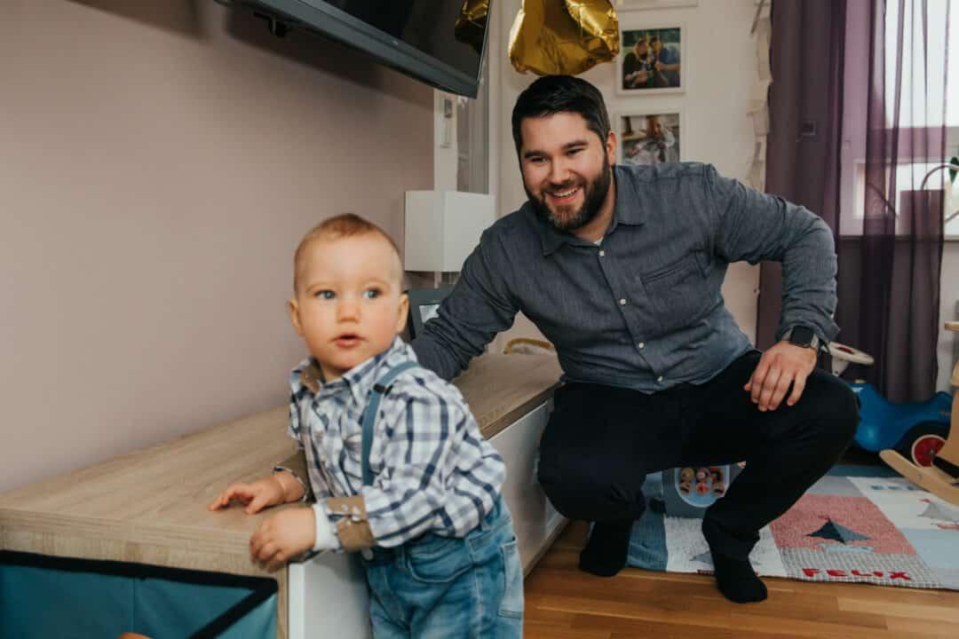 Ein Junge hält sich an einem Sideboard fest und sein Vater kniet hinter ihm.