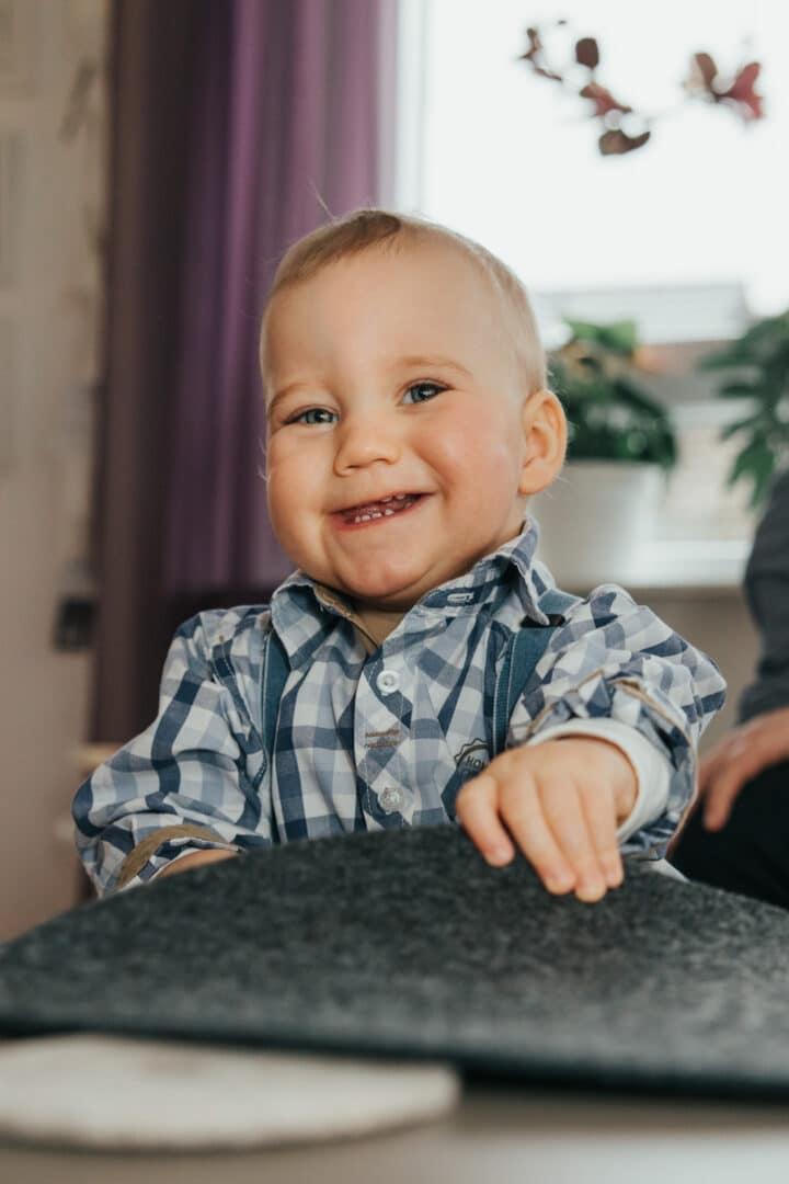 Ein Junge lacht in die Kamera beim Fotoshooting zuhause
