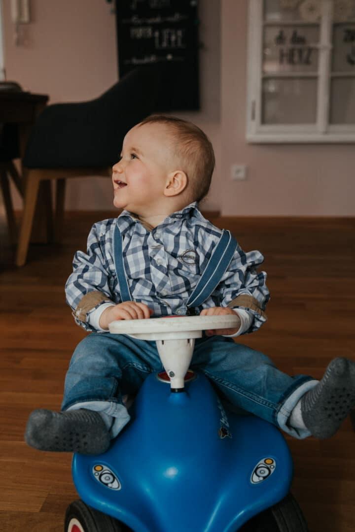 Ein Junge im Carohemd sitzt lachend auf einem blauen Bobbycar