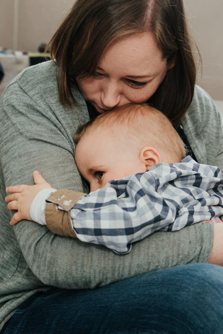 Eine Mutter hält ihren kleinen Jungen ganz fest im Arm und tröstet ihn.