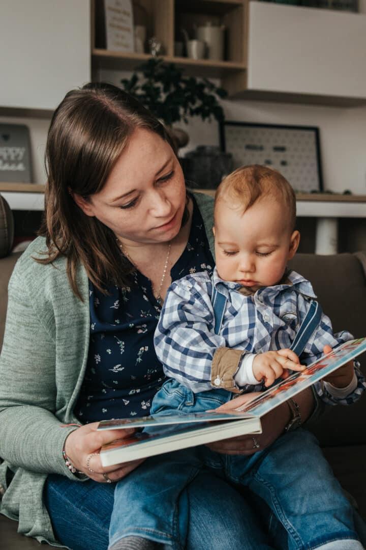 Eine Mutter sitzt auf dem Sofa und schaut mit ihrem Jungen ein Bilderbuch an.