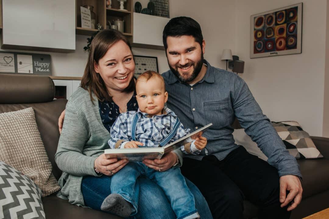 Eine Familie sitzt zusammen auf dem Sofa und lacht in die Kamera während sie ein Buch halten.
