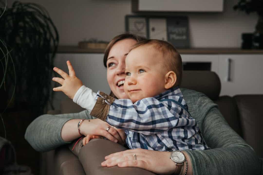 Ein kleiner Junge sitzt mit seiner Mutter auf dem Sofa und sie schauen aus dem Fenster während der Junge etwas zeigt.