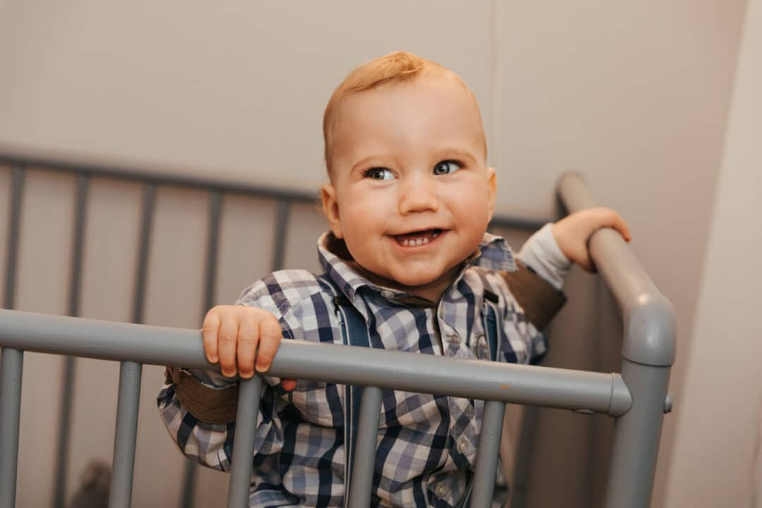 Ein kleiner Junge steht in seinem Gitter Kinderbett und lacht schelmisch