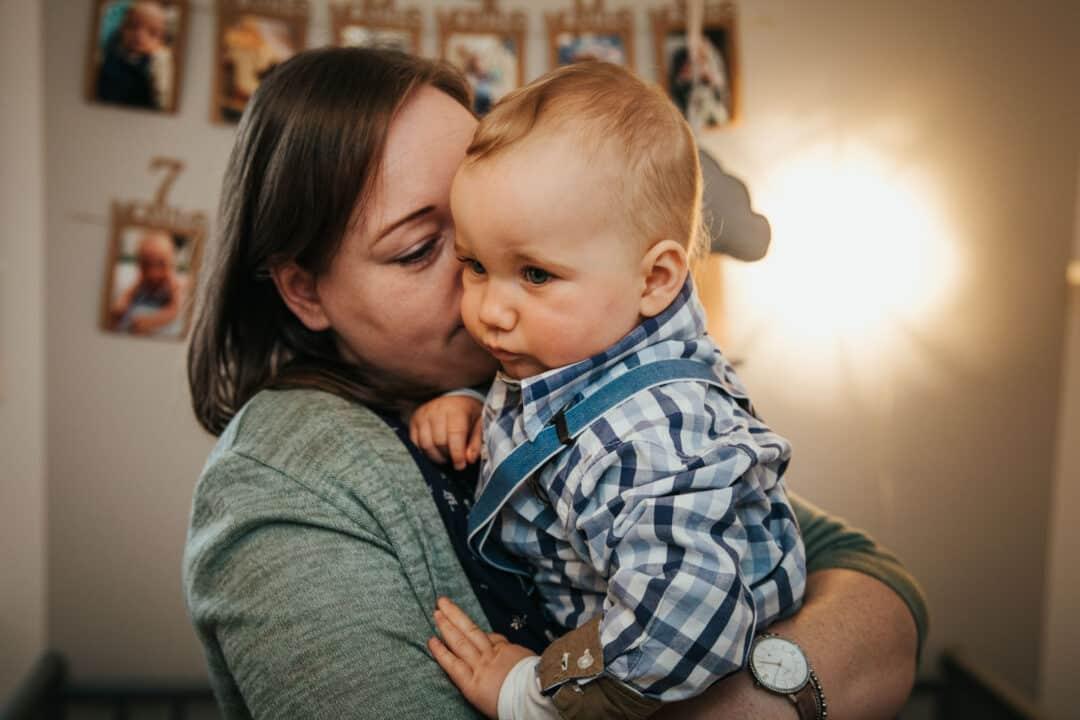 Ein kleiner Junge wird von seiner Mama auf dem Arm getröstet