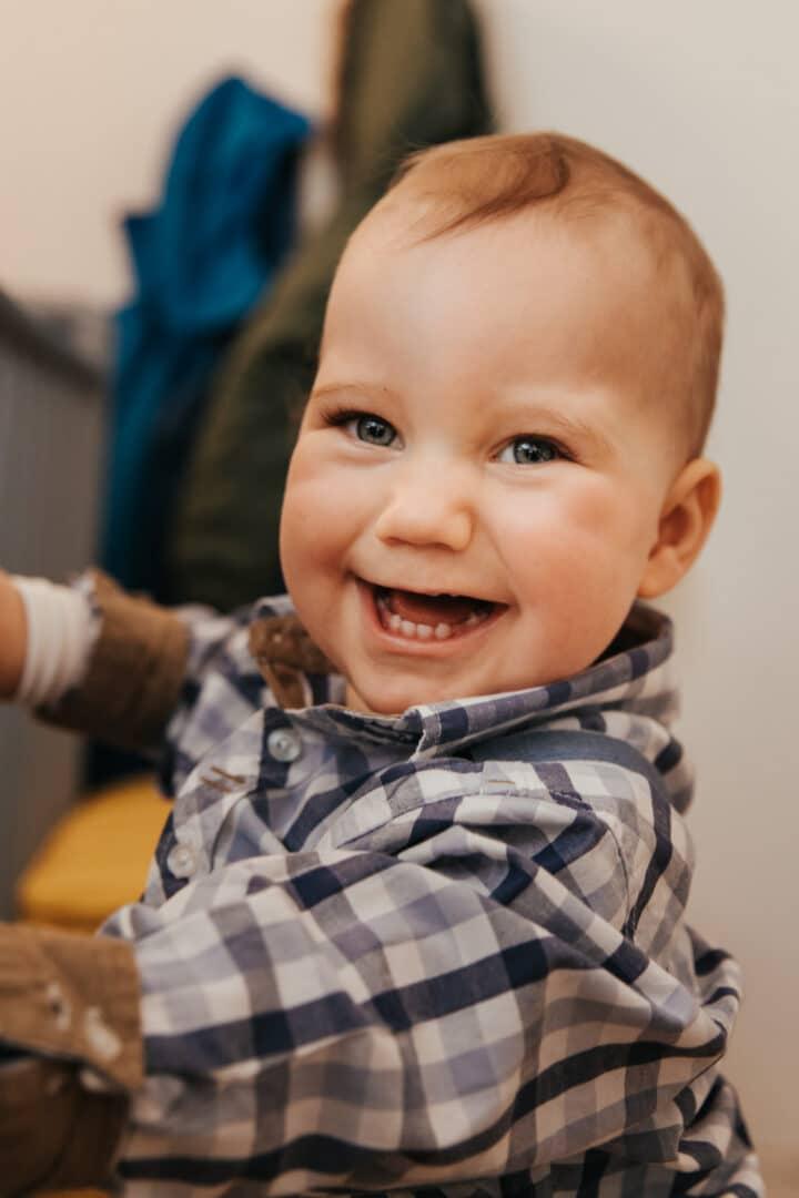 Ein kleiner Junge 1 Jahr alt lacht in die Kamera und zeigt Zähne