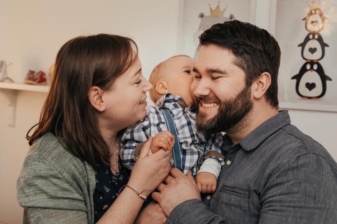 Vater, Mutter und kleiner Junge knuddeln im Gruppenfoto und lachen.