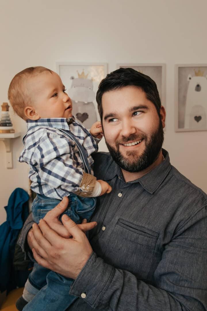Ein kleiner Junge im Carohemd blau zieht am Ohr seines Vaters