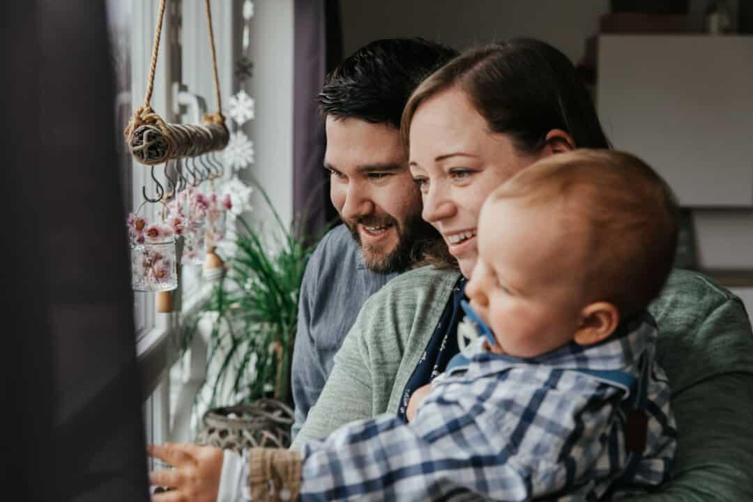 Eine Familie zu dritt schaut mit ihrem kleinen Jungen aus dem Fenster und lachen