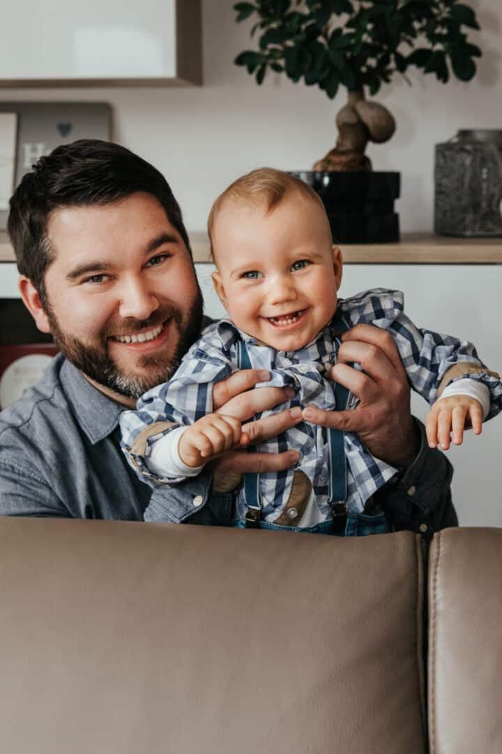 Ein Vater lacht mit seinem Sohn der er hinter dem Sofa hochhebt.