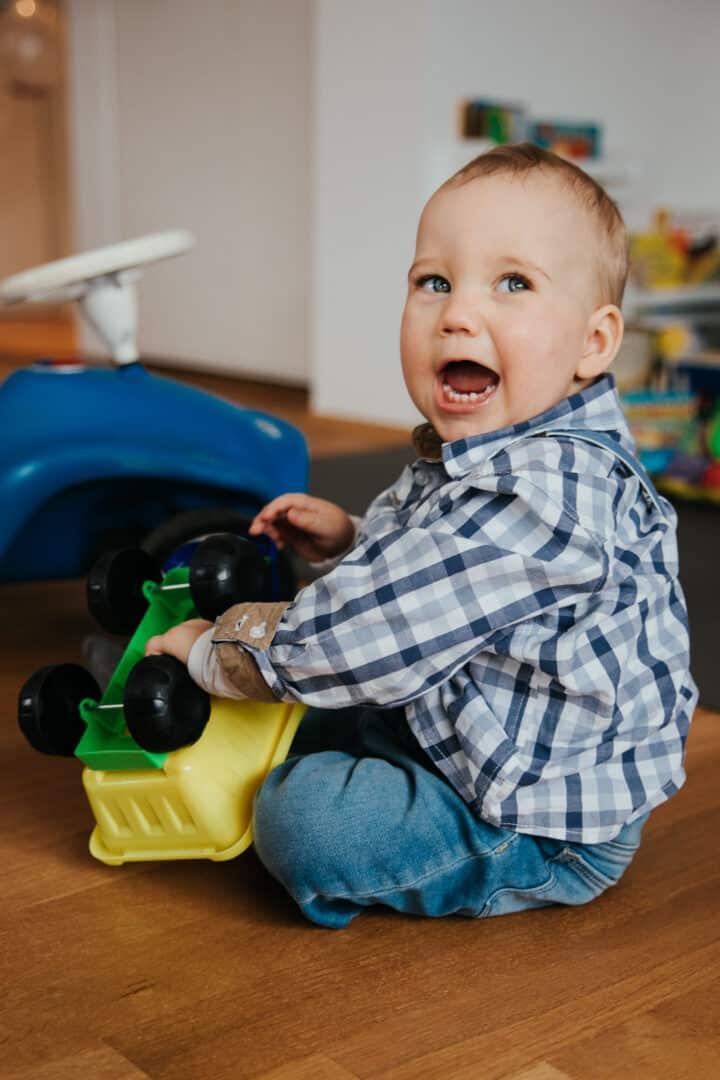 Ein kleiner Junge mit Karohemd sitzt auf dem Boden und lacht und spielt mit einem Bagger in gelb.