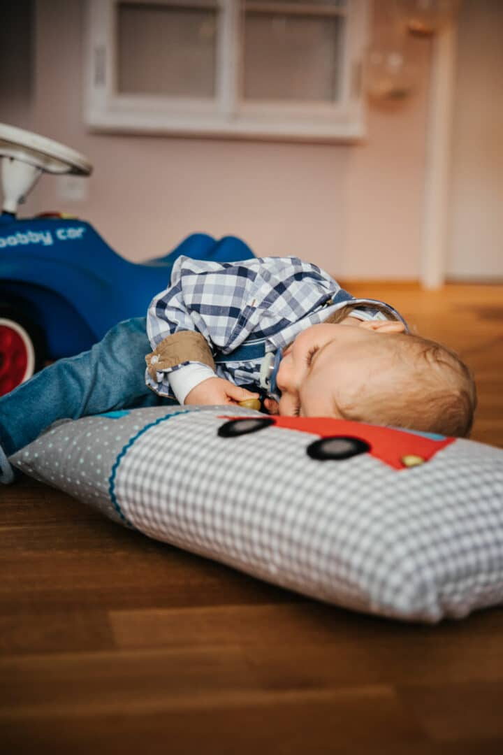 Ein kleiner Junge liegt auf seinem Kissen mit dem blauen Bobbycar im Hintergrund