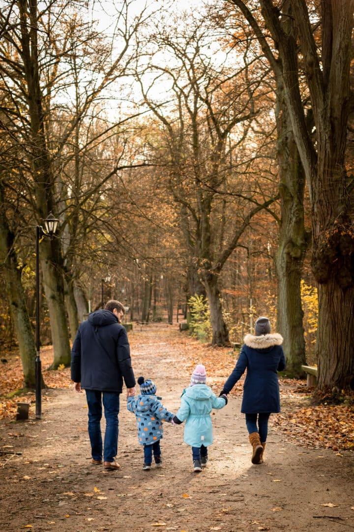 Familie läuft zu viert Händehaltend mit Rücken zur Kamera im Herbstwald