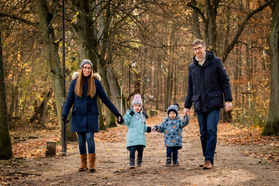 Familie steht zu viert mit Händehalten im Herbstwald und lacht in Kamera