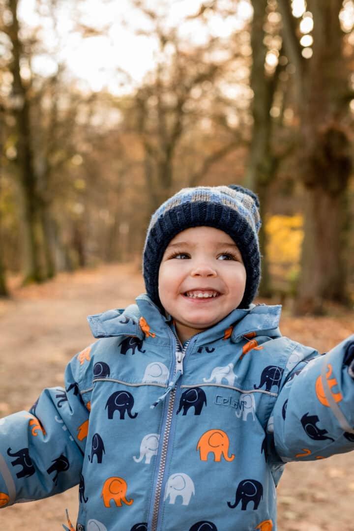 Kleiner Junge in blau wird an Hand gehalten während er durch den Herbstwald läuft