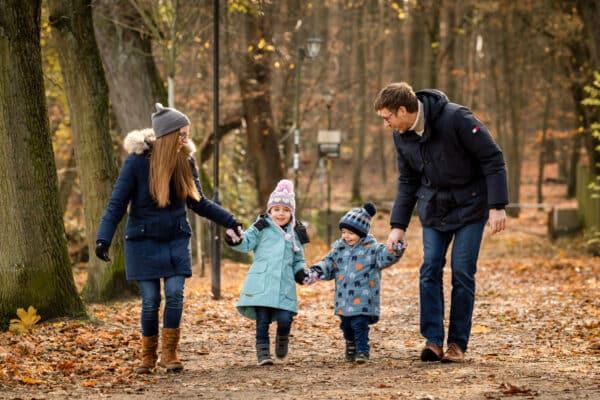Familie zu viert hält ihre Kinder an den Händen und läuft durch das Herbstlaub