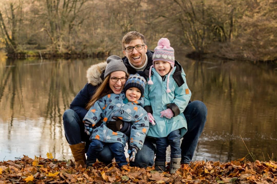 Eine Familie zu viert kniend vor einem Teich mit Herbstlaub