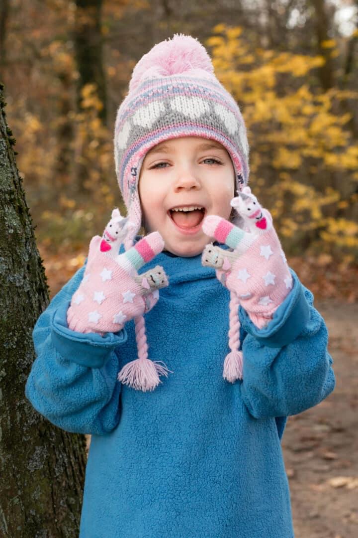 Mädchen mit rosa Muetze und suessen Handschuhen lacht mit Händen in die Kamera im Herbst