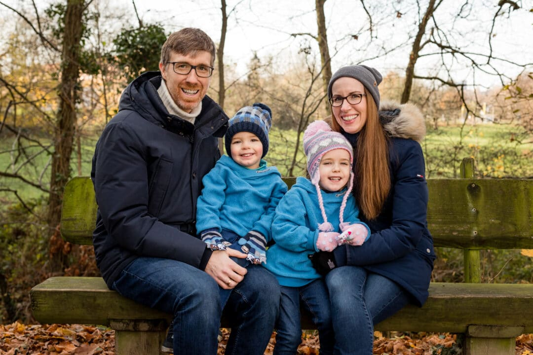 Vater, Mutter, und ihre zwei Kinder sitzen im Herbst auf einer Bank für Familienfotos und lachen