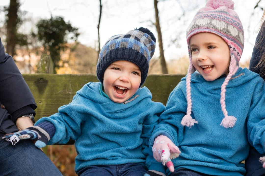 Geschwister sitzen im Herbst mit Mütze auf Bank und lachen