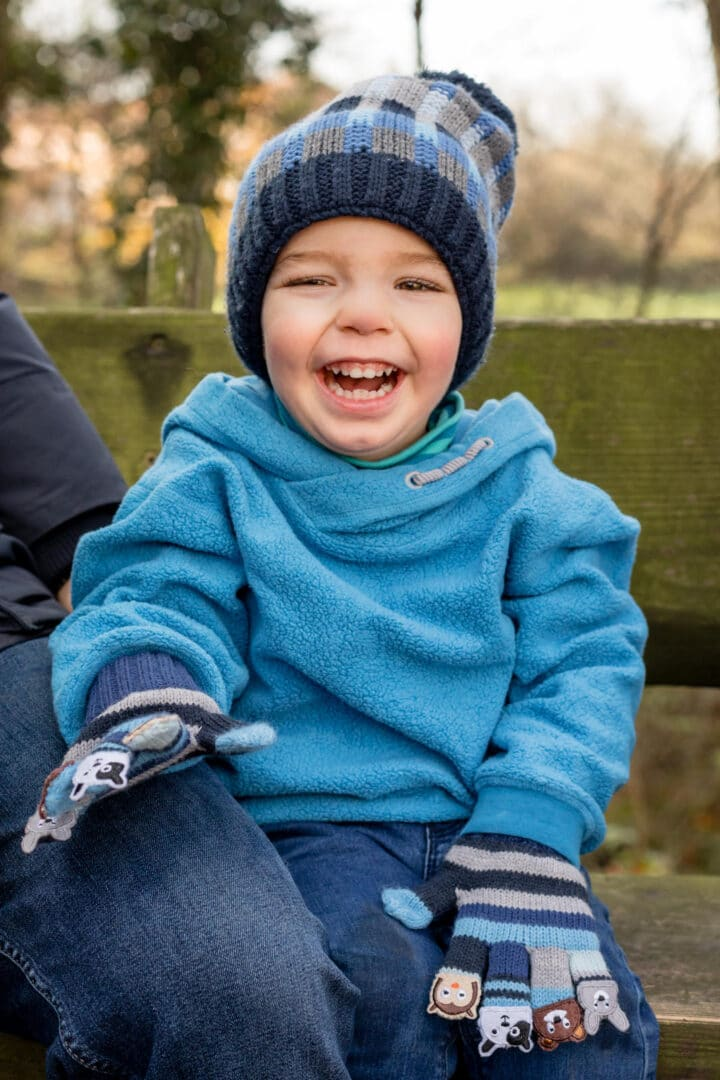 Junge mit blauem Pullover sitzt lachend auf Bank im Herbst