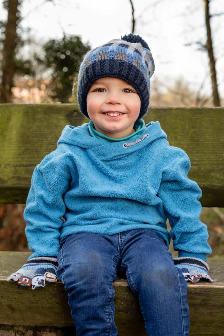 Junge sitzt mit blauer Mütze auf einer Bank im freien und lacht in die Kamera