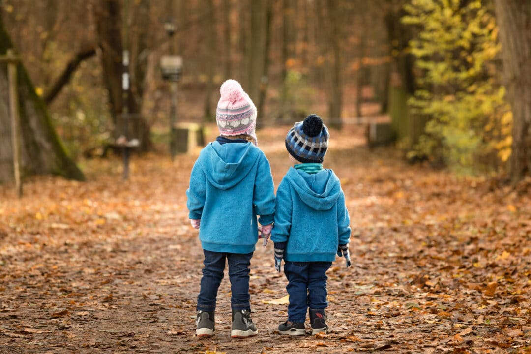 Geschwister stehen mit dem Rücken zur Kamera im Wald bei einem herbstlichen Familienshooting