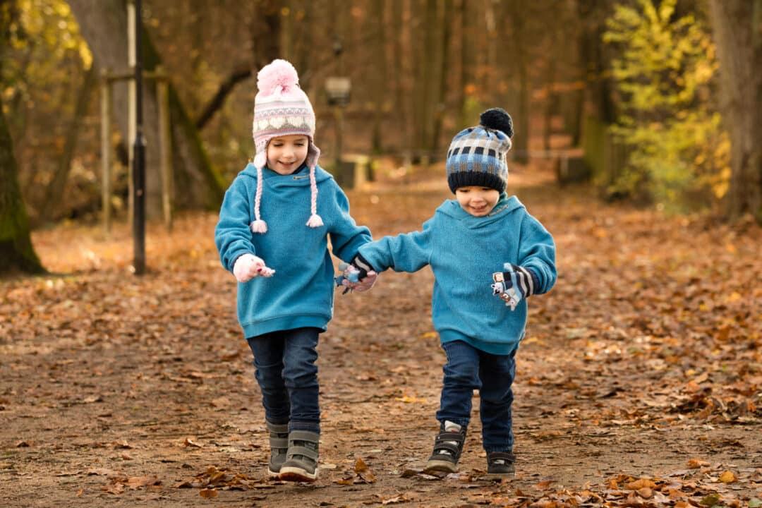Geschwister rennen Hand in Hand im Laub bei einem Kinderfotoshooting in Darmstadt