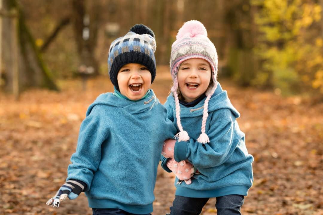 Schwester hält Bruder am Arm zurück und lachen beim Kinder fotoshooting im Herbstlaub