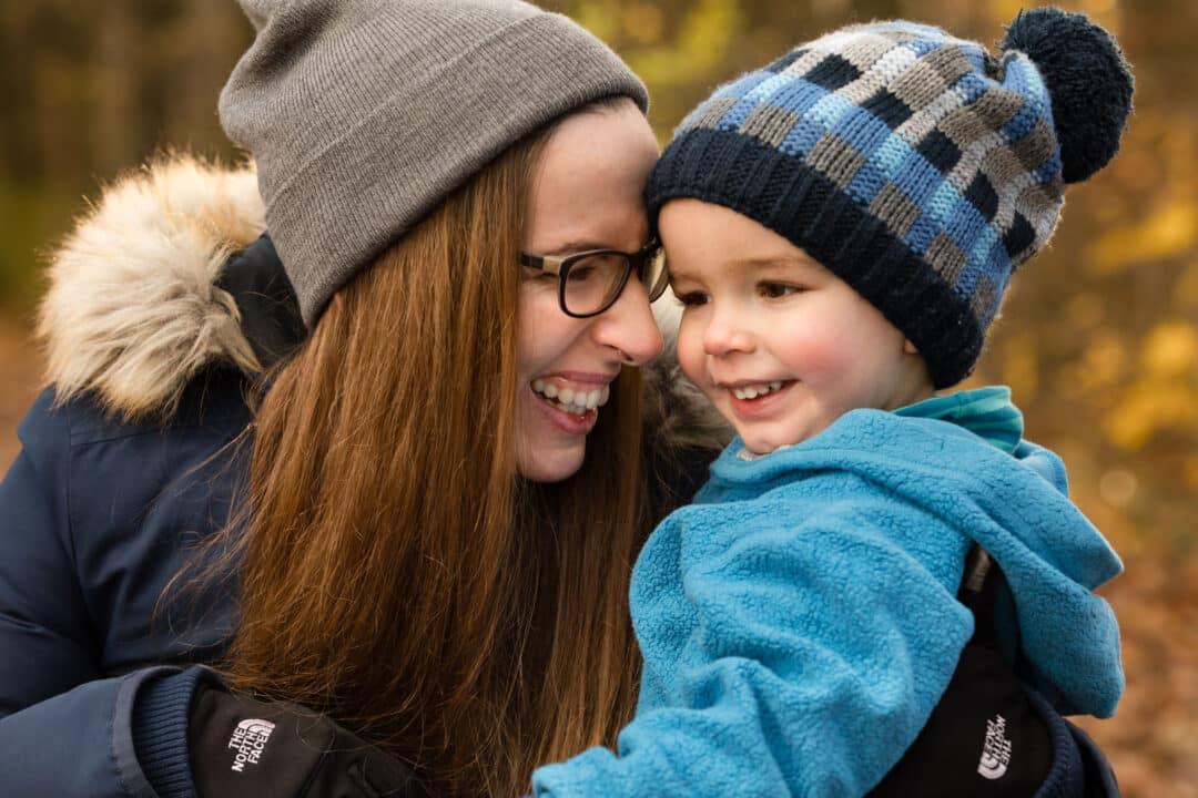 Mutter hält lachenden Sohn auf Arm bei einem herbstlichen Familienshooting in Darmstadt