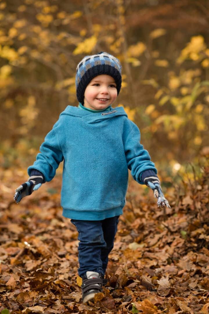 Kleiner lachender Junge läuft im Herbstlaub mit blauem Pullover und Mütze
