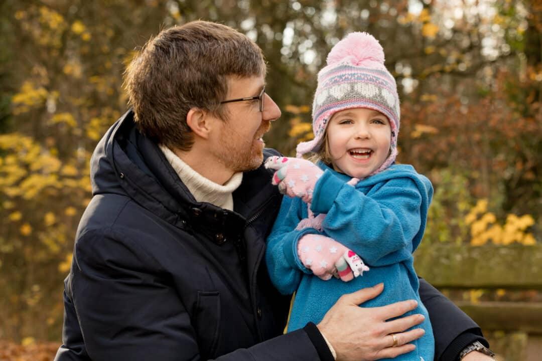 Vater hält lachende Tochter beim herbstlichen Familienshooting am Jagdschloss Kranichstein