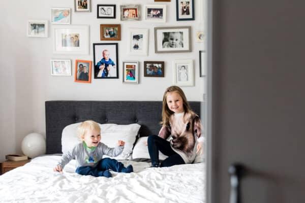 Zwei Kinder toben auf dem Elternbett herum
