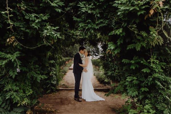 Brautpaar steht unter Pflanzenranken auf der rosenhoehe in darmstadt